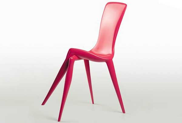 A pink dining chair with two front legs resembling a woman crossing legs at the knee