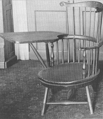 A black and white image of Thomas Jefferson's Swivel Chair made of wood, with a wooden writing arm